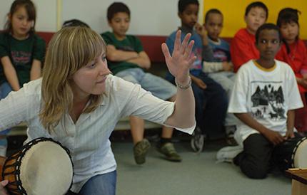 Gillian playing a drum in front of students