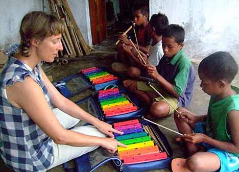 Gillian teaching young children to play the xylophone
